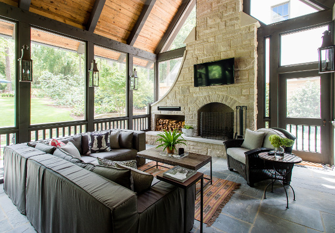 This screened-in porch features a slipcovered outdoor sectional and a gorgeous stone fireplace #screenedporch #screenedinporch #porch #porchfireplace #fireplace #outdoorsectional #outdoorfurniture #outdoorfireplace