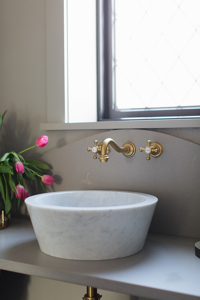 White Marble bathroom vessel sink with grey quartz countertop and brass wall mount faucet all sources on Home Bunch #bathroom #marblesink #vesselsink #wallmountfaucet