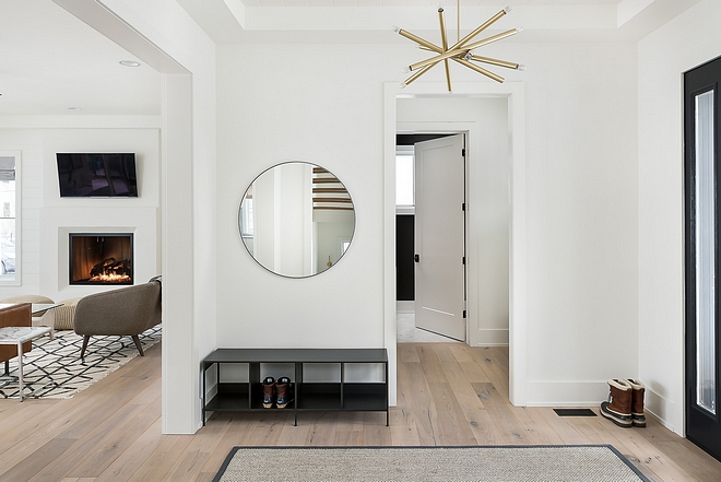 The foyer features White Oak hardwood floors, white walls, modern brass chandelier and a round mirror