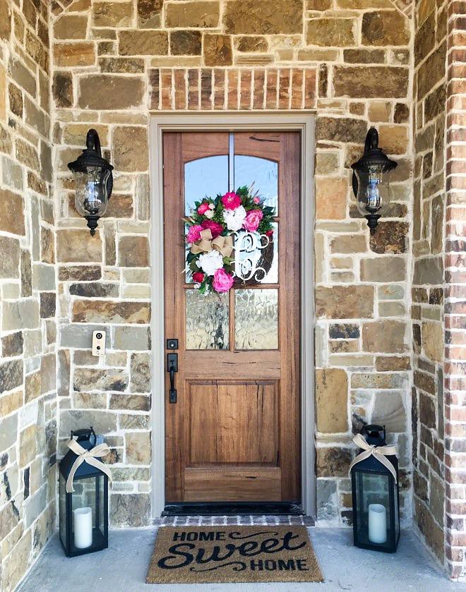 Farmhouse Stone exterior with wood door and brick accent The exterior stone is Oklahoma Chopped