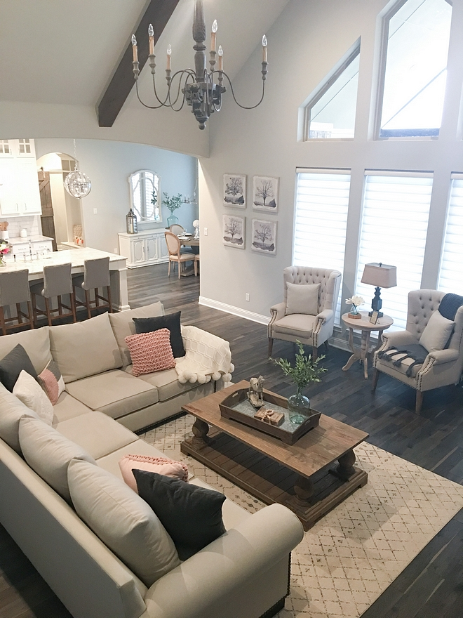 Farmhouse Living Room Vaulted Ceiling with Beams and French Chandelier Paint Color Sherwin Williams Repose Gray SW 7015 Wall Color Sources on Home Bunch #Farmhouselivingroom #Farmhouse #livingroom #vaultedceiling #beamceiling #beamvaultedceiling