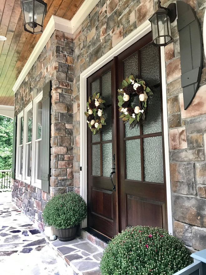 Stone exterior porch with double wood and glass front door sources on Home Bunch