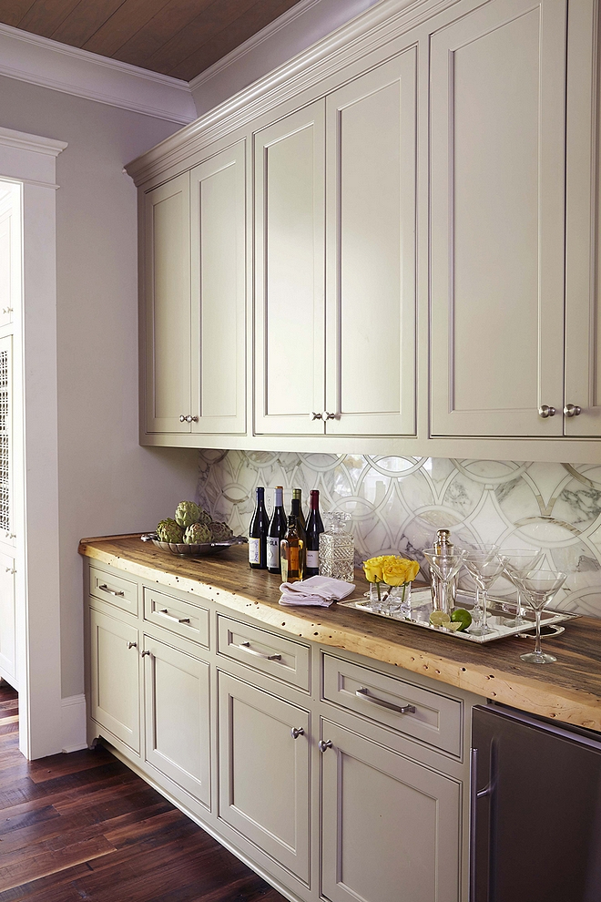 This stunning butler's pantry features grey cabinets, painted in Senora Gray by Benjamin Moore and live edge countertop. Backsplash is the same used in the kitchen
